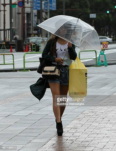 A pedestrian runs in the wind and rain delivered by Typhoon Vongfong on October 13 2014 in Himeji Japan According to the Japan Meteorological Agency...