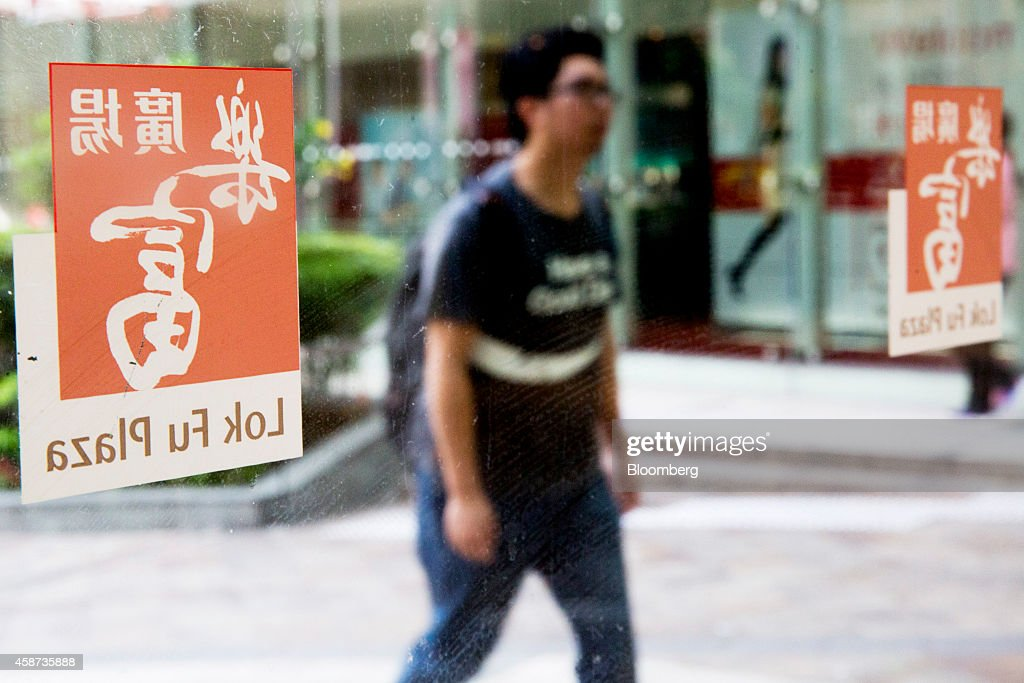 A pedestrian, seen through a glass, walks toward an entrance of Lok Fu Plaza, operated by the Link Real Estate Investment Trust (REIT), in Hong Kong, China, on Monday, Nov. 10, 2014. The Link REIT, Asia's largest property trust which owns neighborhood malls, food markets, and car parks, is scheduled to announce interim results on Nov. 13. Photographer: Brent Lewin/Bloomberg via Getty Images