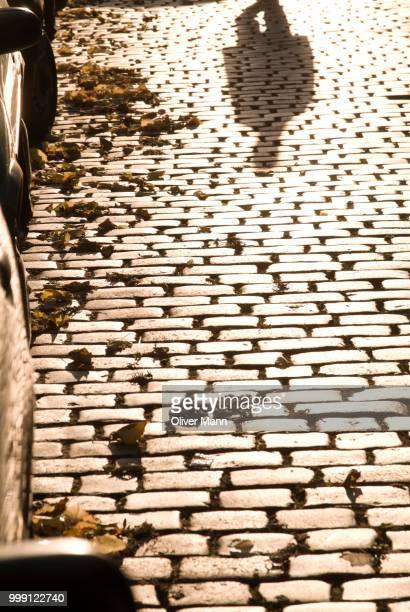 Pedestrian, shadow on cobblestones, Berlin, Germany