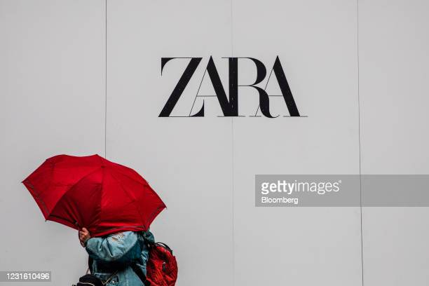 Pedestrian sheltering under an umbrella passes a Zara clothing store, operated by Inditex SA, in Barcelona, Spain, on Monday, March 8, 2021. Inditex...