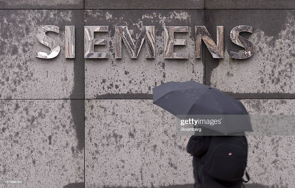 A pedestrian shelters beneath an umbrella while passing a sign outside the Siemens AG headquarters in Munich, Germany, on Monday, Jan. 23, 2012. Siemens AG has earmarked more than 1 billion euros ($1.3 billion) to expand production of gas-turbines and fend off General Electric Co. as they jostle for share of the expanding market. Photographer: Guenter Schiffmann/Bloomberg via Getty Images