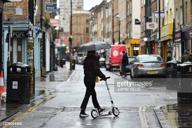 Pedestrian shelters from the rain as she crosses the road with a scooter in east London on October 13, 2020. - Britain's unemployment rate has jumped...