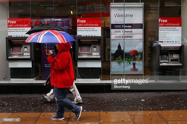 A pedestrian shelters from the rain beneath a British Union flag decorated umbrella as she walks past a HSBC Holdings Plc bank branch in London UK on...