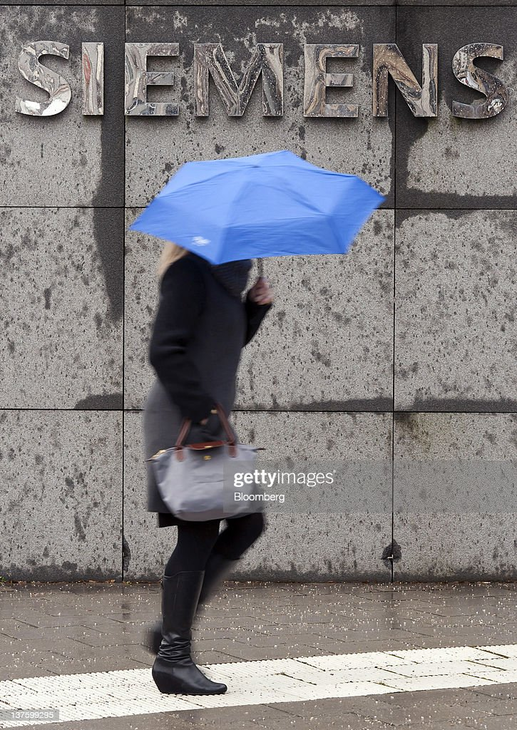 A pedestrian shelters from the rain beneath an umbrella while passing a Siemens AG sign in Munich, Germany, on Monday, Jan. 23, 2012. Siemens AG has earmarked more than 1 billion euros ($1.3 billion) to expand production of gas-turbines and fend off General Electric Co. as they jostle for share of the expanding market. Photographer: Guenter Schiffmann/Bloomberg via Getty Images