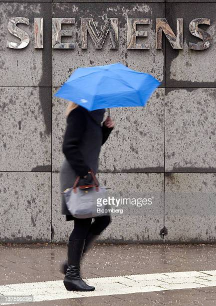A pedestrian shelters from the rain beneath an umbrella while passing a Siemens AG sign in Munich Germany on Monday Jan 23 2012 Siemens AG has...