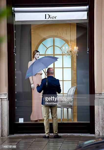 Pedestrian shelters under an umbrella as he looks in the window of a Christian Dior SA store on Maximilianstrasse in Munich, Germany, on Wednesday,...