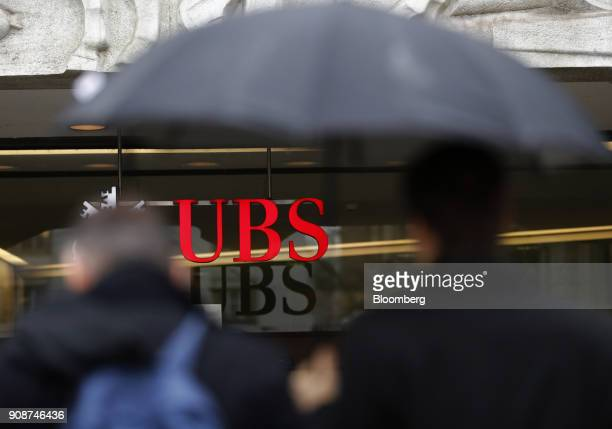 A pedestrian shelters under an umbrella while passing a UBS Group AG bank branch in Zurich Switzerland on Monday Jan 22 2018 A UBS loan backed by...