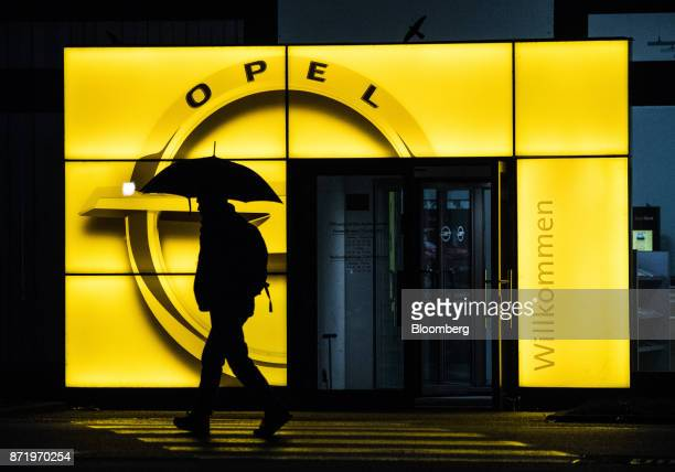 A pedestrian shelters under an umbrella while passing an illuminated Adam Opel AG logo outside the Opel automobile factory in Ruesselsheim Germany on...
