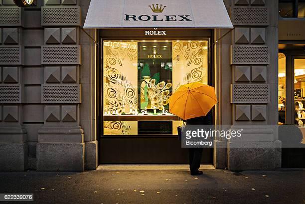 A pedestrian shelters under an umbrella whilst browsing the window of a Rolex Group luxury wristwatch store in Zurich Switzerland on Wednesday Nov 9...