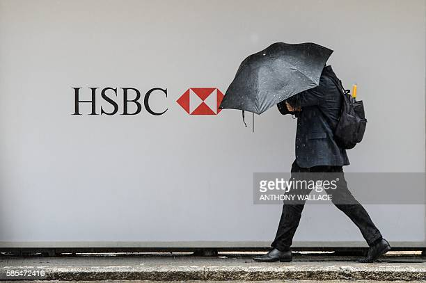 A pedestrian shields himself from the rain as he walks past an HSBC advert in Hong Kong on August 3 2016 HSBC said August 3 net profit plunged in...