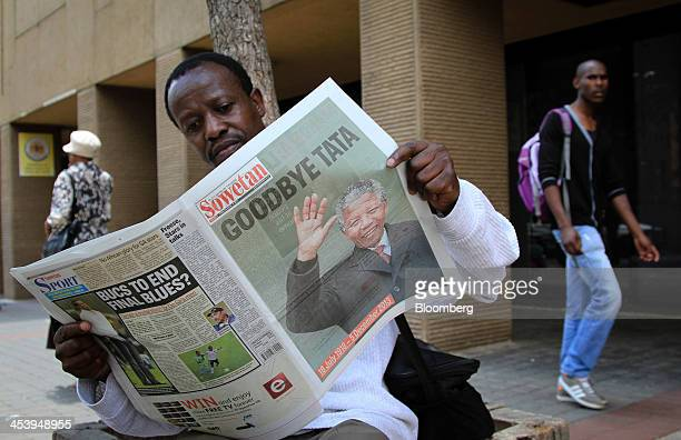 A pedestrian sits and reads a copy of the Sowetan daily newspaper with a front page photograph of the former South African President Nelson Mandela...