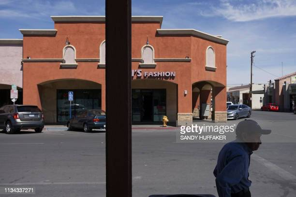 Pedestrian sits in downtown Calexico, California near the Port of Entry to Mexico on April 1, 2019. - US President Donald Trump announced the aid...