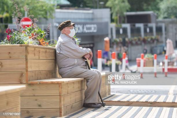 Pedestrian sits on a bench in central in Aberdeen, eastern Scotland on August 5, 2020 following the announcement that a local lockdown has been...