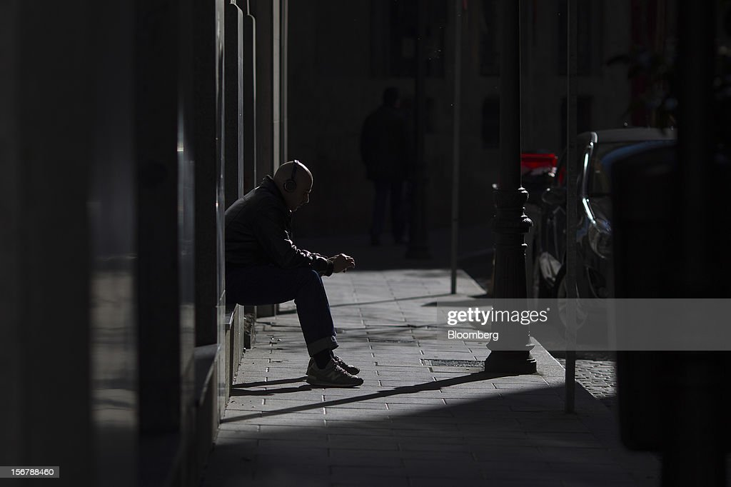 A pedestrian sits on a ledge outside a storefront on Gran Via in central Madrid, Spain, on Monday, Nov. 19, 2012. Bank of Spain Governor Luis Maria Linde said the government risks missing its budget targets this year and next, adding to doubts on Prime Minister Mariano Rajoy's ability to cut the deficit amid a five-year slump. Photographer: Angel Navarrete/Bloomberg via Getty Images