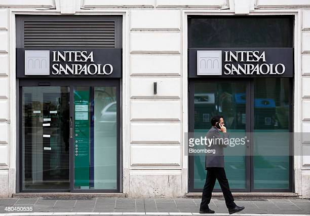 A pedestrian speaks on a mobile handset as he passes an Intesa Sanpaolo SpA bank branch in Rome Italy on Monday March 24 2014 Intesa Sanpaolo Chief...
