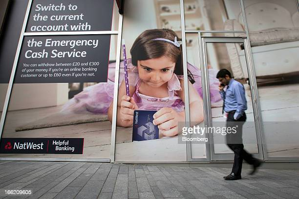 A pedestrian speaks on a mobile phone as he passes a branch of NatWest bank part of the Royal Bank of Scotland Group Plc in London UK on Wednesday...