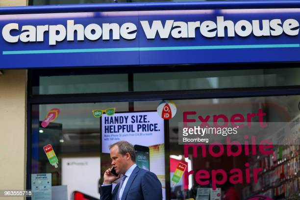A pedestrian speaks on a mobile phone as he passes a Carphone Warehouse retail store operated by DixonsCarphonePlc in central London UK on Tuesday...