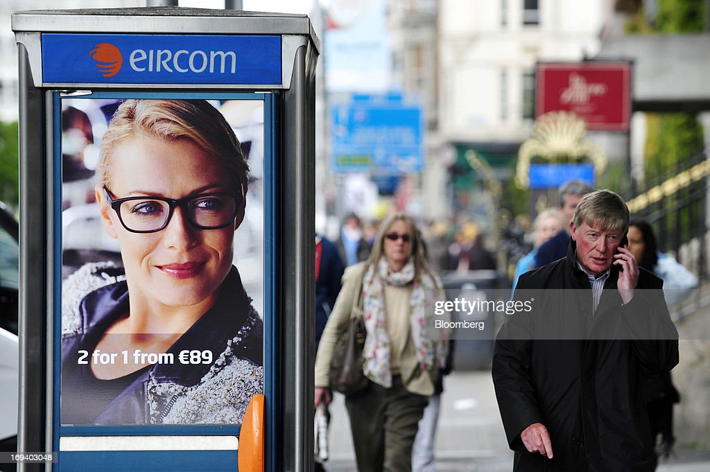 A pedestrian speaks on a mobile phone as he passes an advert for Specsavers Optical Group Ltd. on the door of a fixed-line public telephone booth, operated by Eircom Group, in Dublin, Ireland, on Thursday, May 23, 2013. Eircom Group, which has changed ownership six times since 1999, 'would like to be consolidators rather than consolidated' amid expected mergers and acquisitions in the Irish telecoms market, its Chief Financial Officer Richard Moat said. Photographer: Aidan Crawley/Bloomberg via Getty Images