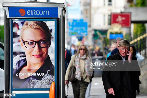 A pedestrian speaks on a mobile phone as he passes an advert for Specsavers Optical Group Ltd on the door of a fixedline public telephone booth...