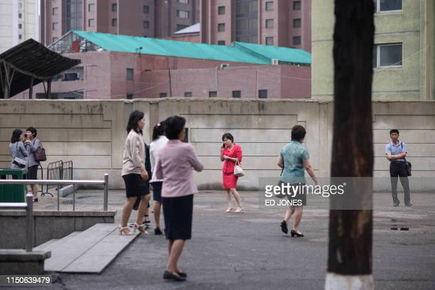 A pedestrian speaks on a mobile phone outside a subway station in Pyongyang on June 19 2019