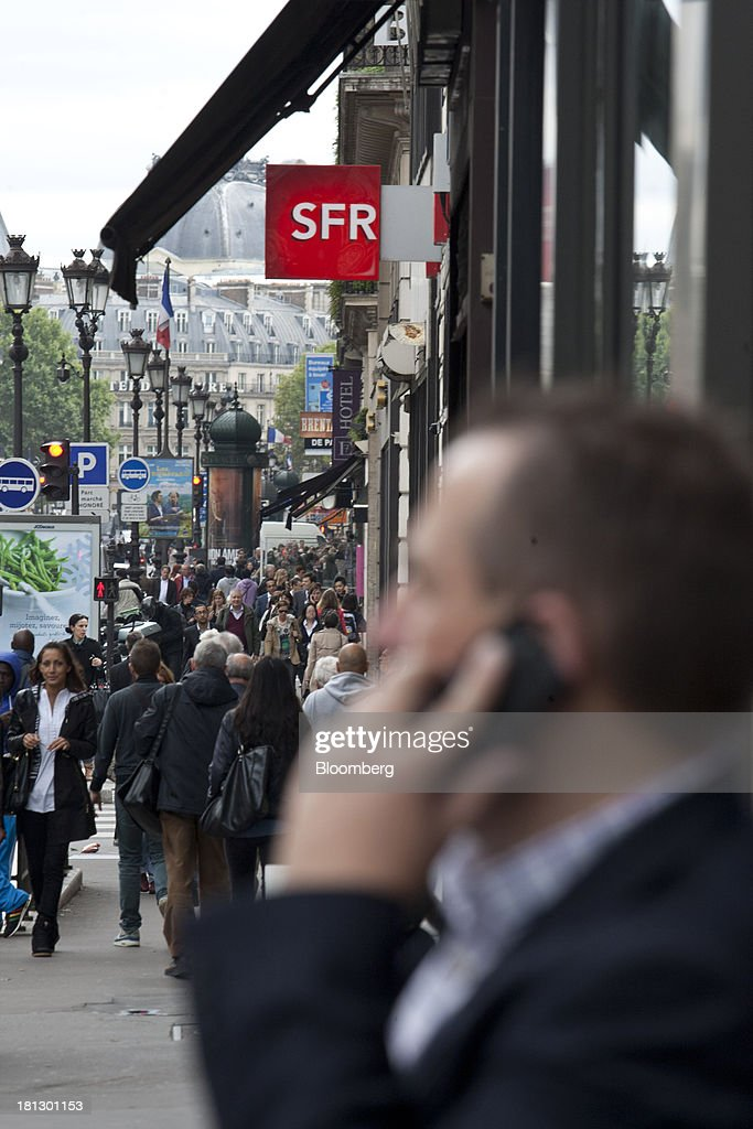 A pedestrian speaks on a mobile phone outside an SFR store, a mobile-phone unit of Vivendi SA, on a busy street in Paris, France, on Thursday, Sept. 19, 2013. Bank of France General Council member Bernard Maris said France will end up restructuring its debt as tax 'optimization' by large companies including Google Inc. will leave too big a burden on the middle class. Photographer: Balint Porneczi/Bloomberg via Getty Images