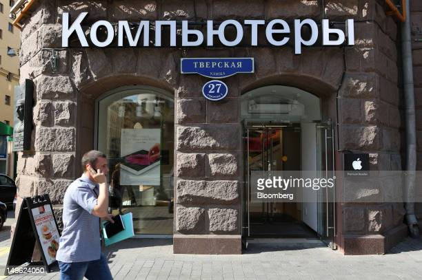 A pedestrian speaks on a mobile phone while passing a reStore a premium Apple product reseller in Moscow Russia on Wednesday Aug 1 2012 OAO Mobile...