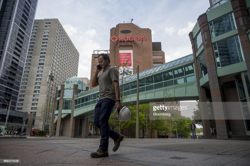 A pedestrian speaks on a smartphone while passing in front of Rogers Communications Inc. headquarters in Toronto, Ontario, Canada, on Wednesday, May 17, 2017. Rogers Communications, Canada's largest wireless carrier, is leveraging organic growth in the country's wireless market to expand its subscriber base. Photographer: Brent Lewin/Bloomberg via Getty Images