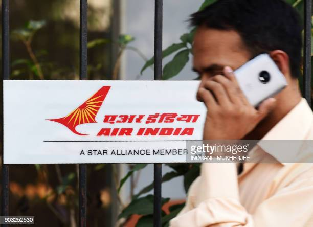 A pedestrian speaks on his phone next to a sign of state carrier Air India outside its headquarters in Mumbai on January 10 2018 Indian lawmakers...