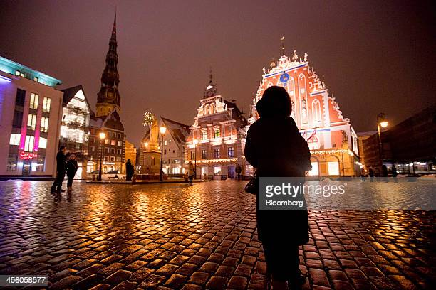 A pedestrian stands in the town square near the House of the Blackheads top in Riga Latvia on Wednesday Dec 11 2013 The country of 2 million will...