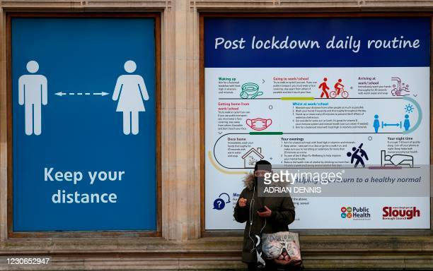 Pedestrian stands next to hoarding with advice on how to stay safe during the Covid-19 pandemic on the high street in Slough, west of London, on...