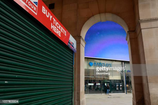 A pedestrian stands outside a Barclays Plc bank branch near a closed tourist sightseeing tour ticket booth in London UK on Monday July 27 2020 The...
