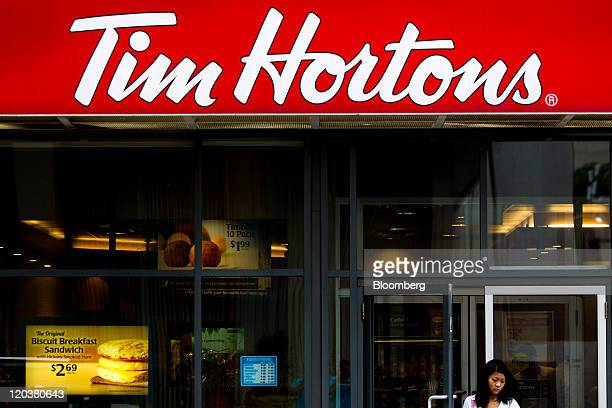 A pedestrian stands outside of a Tim Hortons Inc restaurant in Toronto Ontario Canada on Wednesday Aug 3 2011 Tim Hortons Inc is a chain of franchise...