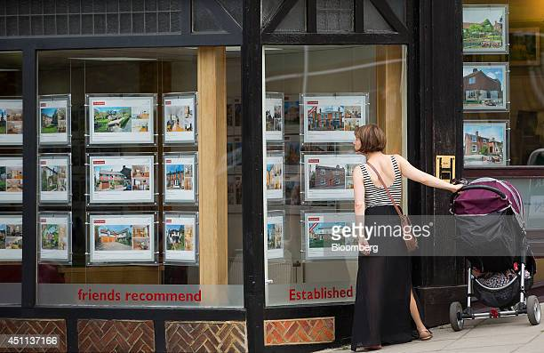 A pedestrian stands with a baby stroller as she looks at information leaflets of residential properties displayed for sale in the window of an estate...