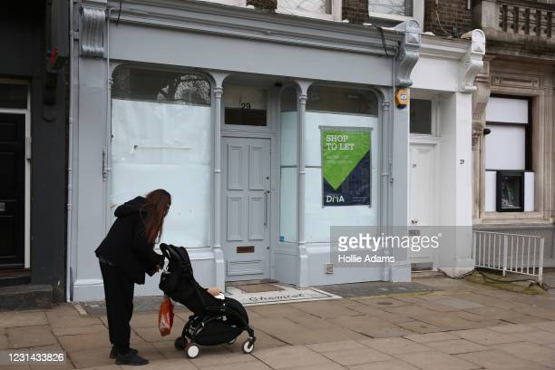 Pedestrian stops outside a shop which is currently advertised as to let on Hampstead High Street on February 28, 2021 in London, England. In its...