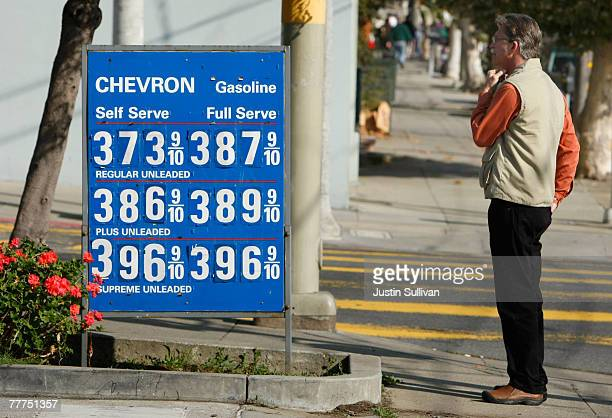 A pedestrian stops to look at gas prices nearing $400 per gallon displayed at a Chevron service station November 6 2007 in San Francisco California...