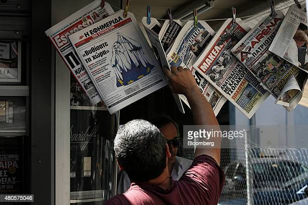 A pedestrian stops to read the front page of a newspaper hanging outside a magazine kiosk in Thessaloniki Greece on Monday July 13 2015 Greece has...
