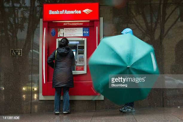 A pedestrian stops to use a Bank of America Corp automated teller machine in San Francisco California US on Wednesday March 14 2012 Wells Fargo Co...