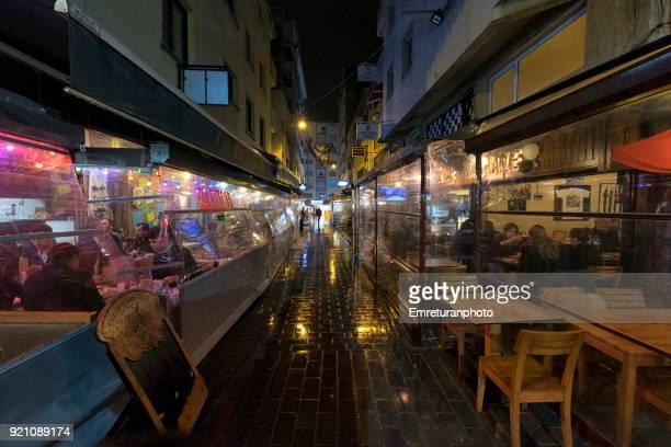 Pedestrian street with restaurants on both sides on a rainy night,Izmir.