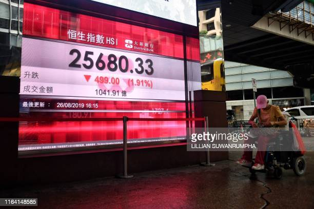 A pedestrian strolls past a stocks display board showing the Hang Seng index at 2568033 down 191 percent in Hong Kong on August 26 2019