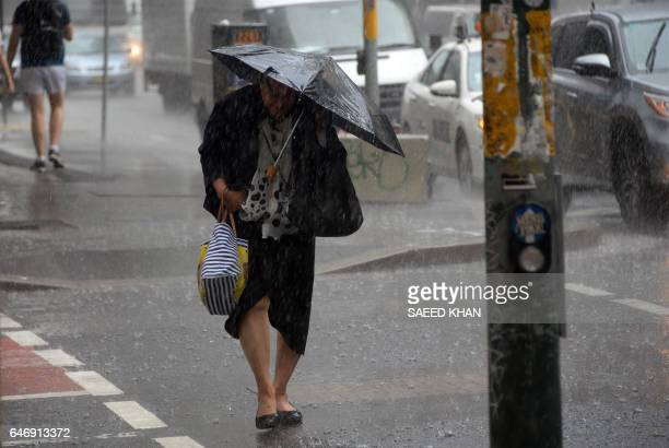 A pedestrian struggles through the heavy rain in the central business districk of Sydney on March 2 2017 / AFP PHOTO / SAEED KHAN