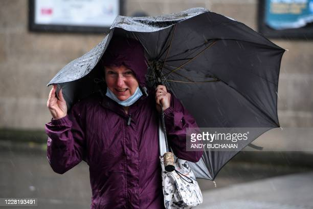 Pedestrian struggles with her umbrella against the wind in Glasgow city centre on August 25 as Storm Francis brings rain and high winds to the UK.