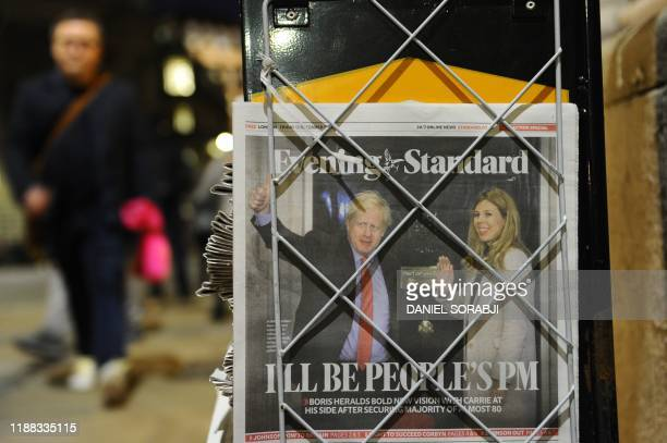 A pedestrian takes a copy of the London Evening Standard newspaper in London on December 14 with the front page reporting on the election victory of...