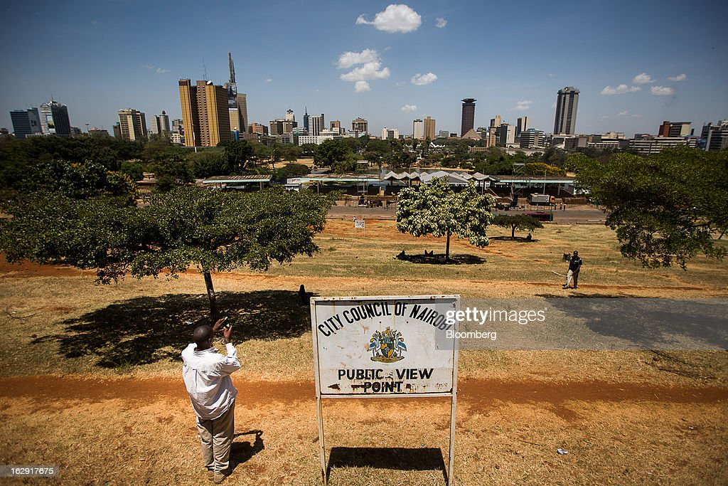 A pedestrian takes a photograph of the city skyline from a public viewpoint at a park in Nairobi, Kenya, on Friday, March 1, 2013. Next week's presidential vote will be the first since disputed elections in 2007 triggered ethnic fighting in which more than 1,100 people died and another 350,000 fled their homes. Photographer: Trevor Snapp/Bloomberg via Getty Images