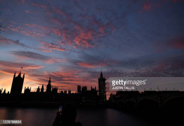 Pedestrian takes a photograph of the Palace of Westminster, comprising both houses of parliament, the House of Commons and the House of Lords, as it...