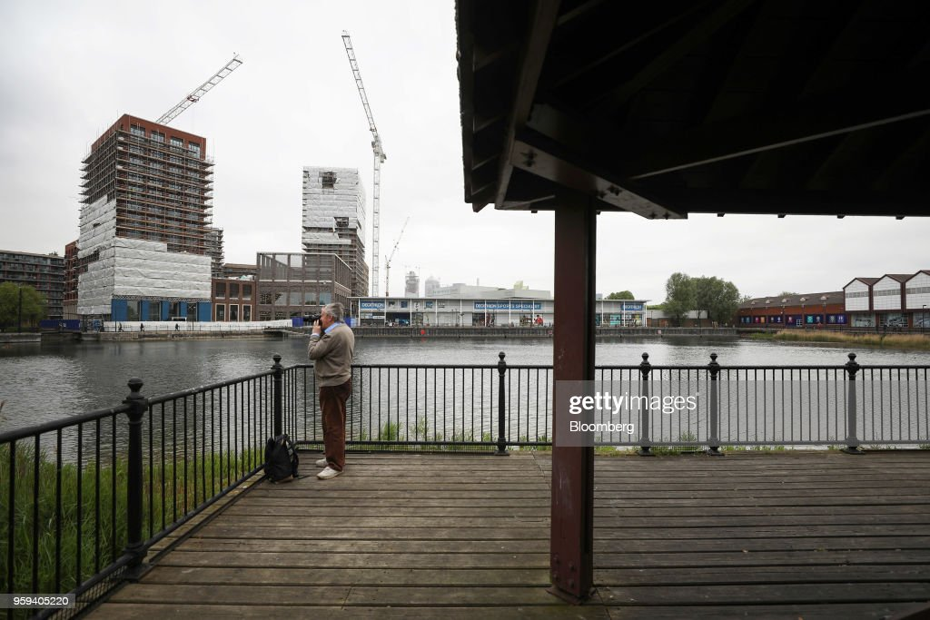 A pedestrian takes a photograph on a pontoon in the Canada Water area of south London, U.K., on Wednesday, May 16, 2018. British Land Co. will seek approval to develop as many as 3,000 homes and work space equivalent to almost four Gherkin skyscrapers on a plot in south Londons Canada Water. Photographer: Chris Ratcliffe/Bloomberg via Getty Images