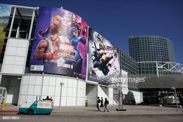 A pedestrian takes a photograph with a smartphone of billboards displaying video game advertisements outside the Los Angeles Convention Center ahead...