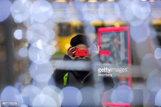 A pedestrian takes a photograph with an Apple Inc iPhone in Berlin Germany on Wednesday Jan 7 2015 As European Central Bank policy makers gather for...