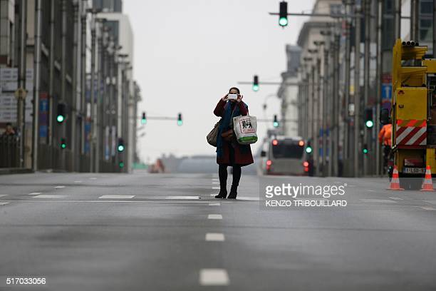A pedestrian takes a picture with her smartphone on a street in the European Quarter near Maelbeek Maalbeek subway station in Brussels on March 23 a...