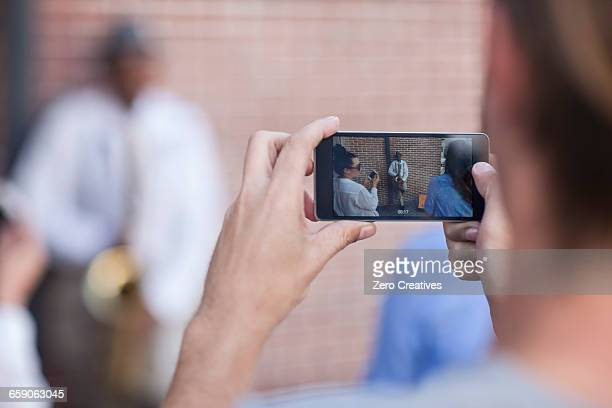 Pedestrian taking photograph of street musician, using smart phone