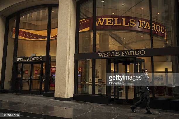 A pedestrian talks on a mobile device while passing in front of a Wells Fargo Co bank branch in New York US on Wednesday Jan 11 2017 Wells Fargo Co...